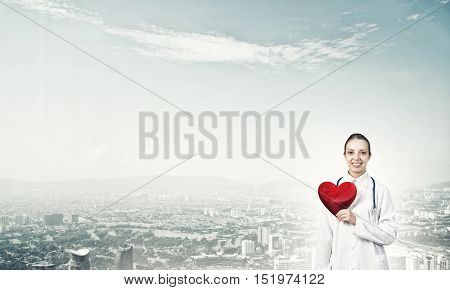 Young woman doctor against city background holding red heart