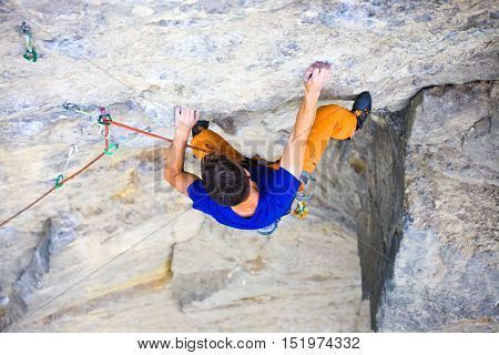 Male Sports And Climbs On The Rock.