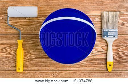 Bucket of paint, paint brush and paint roller on a wooden background
