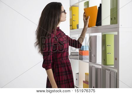 Side view of woman in checkered dress picking a book in office library. Concept of self education and getting new knowledge