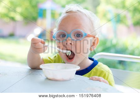 A little boy wearing glasses at an outdoor cafe eating ice cream in summer
