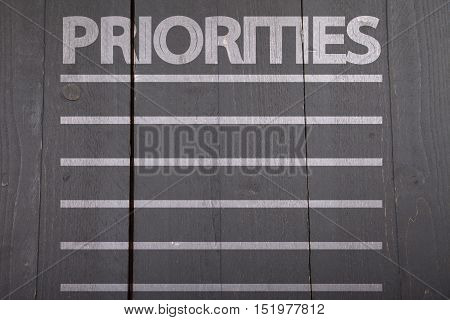 White priorities list on black wooden background