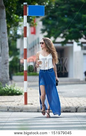 Fashionable girl with take-out coffee crossing road