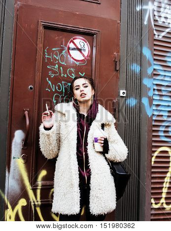 young pretty stylish teenage girl outside in city wall with graffity smoking cigarette at forbidden smoke sighn, lifestyle teen concept protest close up