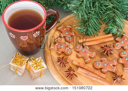 Many gingerbread men on a wooden board and tea for Christmas