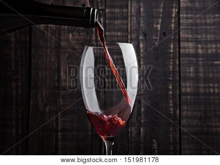 Pouring red wine into the glass from bottle on old wooden background
