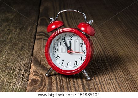 Red alarm clock with at five minutes to midday/ midnight on the wooden table
