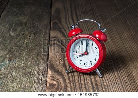 Red alarm clock at eight oclock on the wooden table