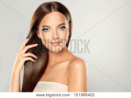 Beautiful brunette girl with long and straight brown hair . Shiny smooth  and healthy well-groomed hair .
