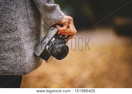 Woman hand with retro analog film camera. Concept for travel, wanderlust, outdoor adventure. Natural fall, defocused, bokeh background. Shallow depth of field