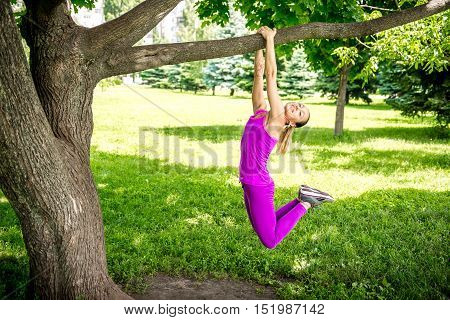 Portrait of a beautiful young woman smiling and hanging on a branch from a tree in the park. Young girl athlete stretches hanging on a branch