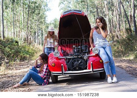 Friends on a roadtrip having a problem with their old car