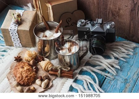 Metal mugs with cacao and marshmallow with different decorations soft focus background