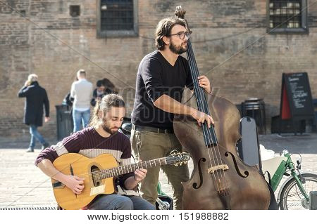 Bologna Italy October 15 2016 - A contrabass street performer and a guitar player play music for the passers