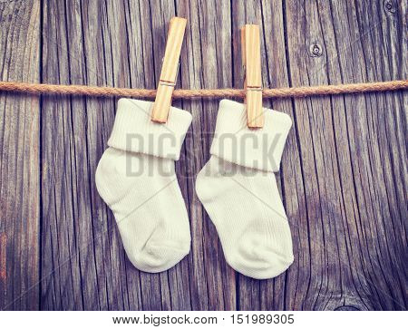 Baby goods hanging on the clothesline. Baby white socks on a clothespin on a wooden background