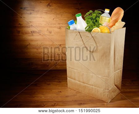 Full paper grocery bag on wooden background with place for text