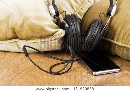 Headphones On Cushions On A Wooden Surface