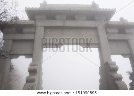 One of Taishans many landmark gates on the summit of Mount Tai in Shandong Province China on a foggy day.