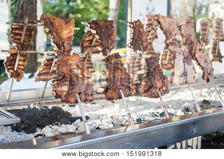 Asado traditional barbecue dish in Argentina roasted meat of beef cooked on a vertical grills placed around fire
