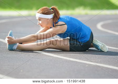 Sport and Athletics Concepts and Ideas. Caucasian Female Sportswoman Having Legs Muscles Stretching Exercises Outdoors. Horizontal Image Composition