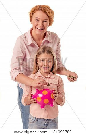 Portrait of cute little girl and her beautiful grandma holding a piggy bank looking at camera and smiling isolated on white