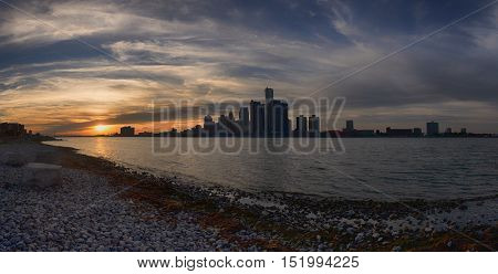 Panoramic view of Detroit skyline from river shoreline at sunset