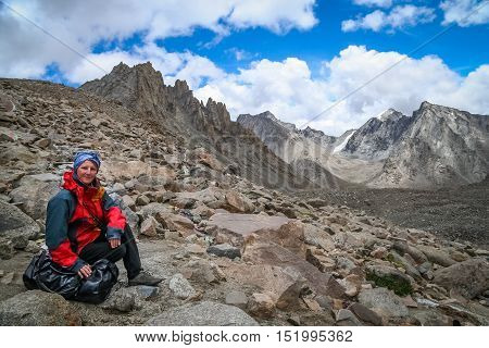 Trekker resting on the top of the high pass nearby Mount Kailash - holy mountain in the Himalaya, Central Tibet
