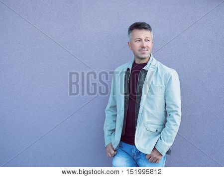 Handsome cheerful mid adult man posing over violet wall. Outdoor male portrait, image toned.