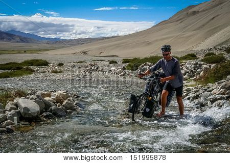 Cyclist crossing the river during journey in the remote part of Tibetan plateau, Tibet