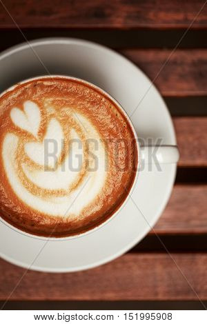 Cup of cappuccino with latte art on wooden table. Top view, macro.