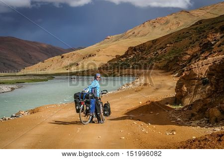 Single female cyclist on the bicycle in the stunning remote part of Western Tibet