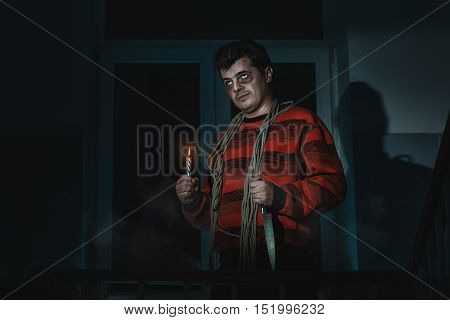 Horrible man with a knife and a noose around his neck standing in the room.