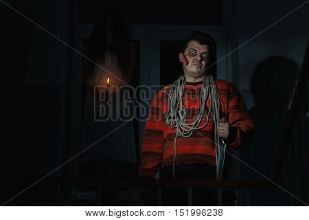 Horrible man with a knife standing in the room a woman is a ghost behind him.