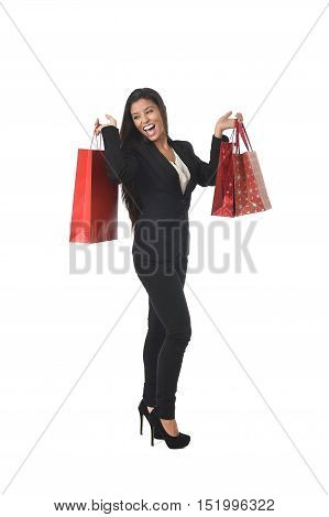 young happy beautiful latin woman in fancy elegant suit holding sale shopping bags excited and cheerful isolated on white background in shopaholic and fashion lover concept