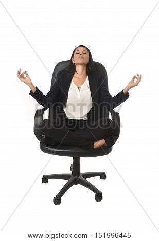 young beautiful latin american business woman sitting at office chair in lotus posture practicing yoga and meditation isolated on white background