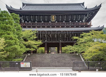 Kyoto Japan - September 16 2016: The wooden monumental gate to Chion-in Buddhist Temple in the largest one of its era in Japan. Flanked by trees under cloudy sky.