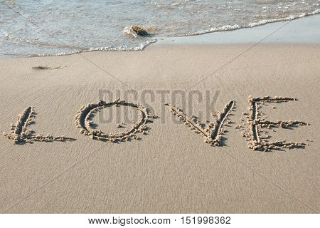 Love written in the sand on the beach