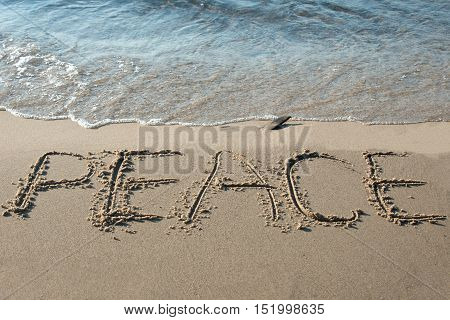 Peace written in the sand on the beach