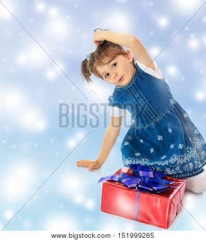 Charming little girl in a blue dress with short sleeves , kneeling around a red box with a blue bow.Blue Christmas festive background with white snowflakes.