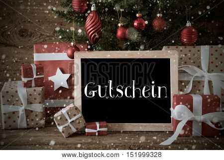 Nostalgic Christmas Card For Seasons Greetings. Christmas Tree With Balls And Snowflakes. Gifts In The Front Of Wooden Background. Chalkboard With German Text Gutschein Means Voucher