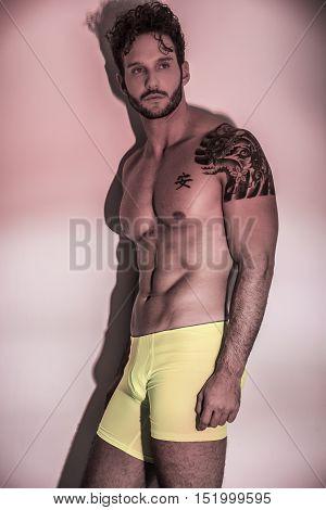 Handsome shirtless muscular man, standing, on light background in studio shot