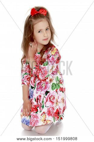 Gentle little girl with a long ponytail down to his shoulders, and a red bow on her head, in a beautiful summer dress. The girl kneels on the floor and straightens his arm hair