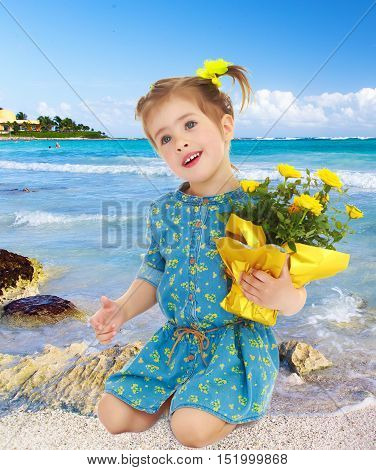 Beautiful little girl in a blue short dress. Girl kneeling with a beautiful bouquet of yellow flowers.On the background of white, sandy beaches, blue sky and clouds. Summer family vacation.