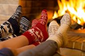 Family in socks near fireplace in winter or christmas time poster