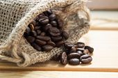 stock photo of prone  - Close up of a hessian sack containing whole coffee beans spilling on to wooden table.