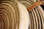 stock photo of firehose  - Antique Fire Hose rolled up on display in Fire Museum - JPG