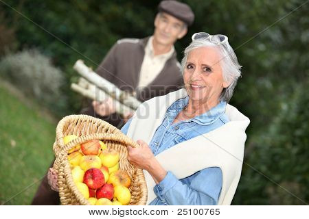 Elderly couple collecting objects in the forest