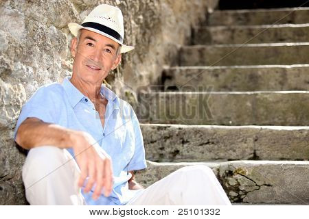 Senior man sitting on some old stone steps
