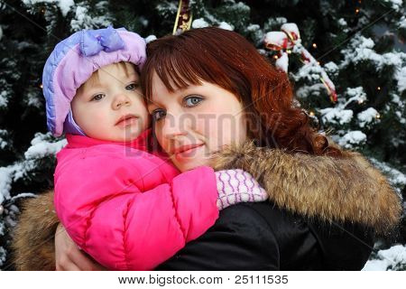 Young woman with small daughter stands near green tree with snow