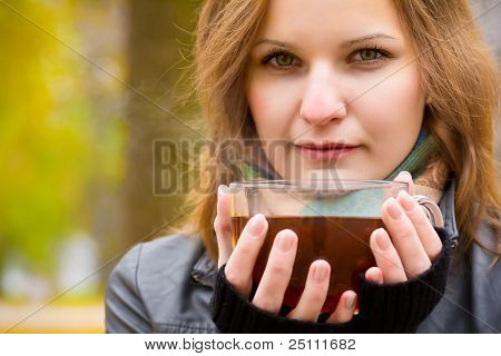 Girl holds large cup with hot tea